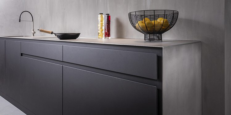 Fenix keuken, zwarte keuken met stalen blad, aanrechtblad van staal. Moderne design keuken van B DUTCH. B DUTCH maakt keukens op maat. Luxe keukens van Fenix of Corian wit. Bij de tijdloze keukendesigns van B DUTCH gebruikt B DUTCH ook massief hout of fineerhout. Voor keukenkasten, achterwanden van keukens, geintegreerde eettafels, etc.