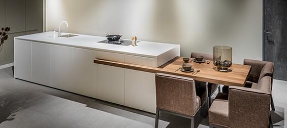 Corian kookeiland, wit keukeneiland met geïntegreerde massief houten eettafel of bar. Tijdloze keuken op maat, B DUTCH design keuken. Kom keuken inspiratie opdoen in onze fabrieksshowroom in Cuijk.