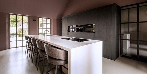 Corian keuken B DUTCH. Maatwerk Corian keuken met Solid Surface Corian mat wit kookeiland en strakke kastenwand met inbouwapparatuur.
