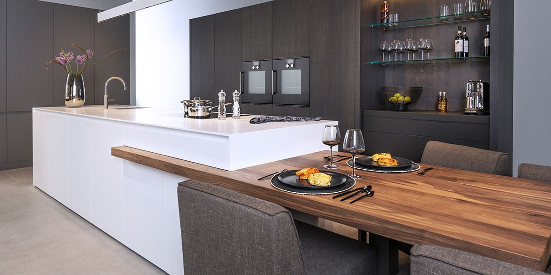 Corian kookeiland met houten tafelblad B DUTCH. Strak design solid surface Corian keukenblok, kook eiland. Met strakke keuken achterwand met kasten en keuken apparatuur.